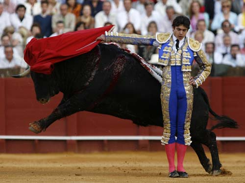French matador Sebastian Castella performs a backpass on a bull during a bullfight in the Maestranza bullring in Seville